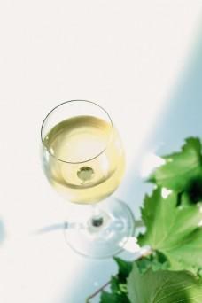 葡萄叶旁的一杯葡萄酒图片