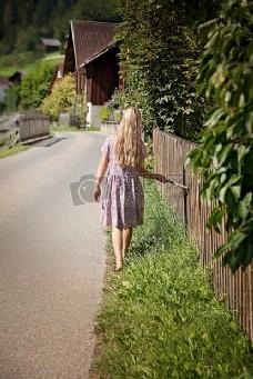 女孩在白色和紫色长裙白天路上行走绿草场