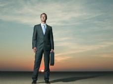 在沙漠中提着皮箱的商业男人图片