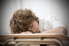 在课桌上休息的卷发男孩图片